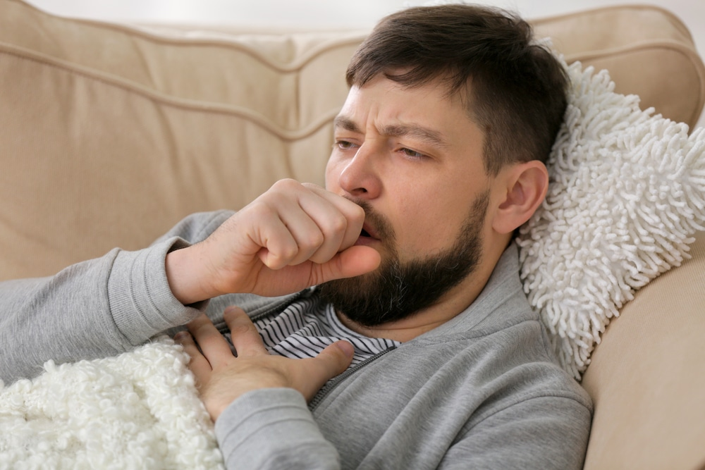 Young ill man lying on sofa at home